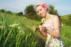 一个愉快的年轻逗人喜爱的女孩的画象有多彩多姿的头发的在乡下公路旁边收集花在日落 的treadled 免版税库存照片