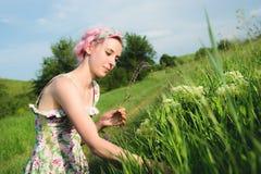 一个愉快的年轻逗人喜爱的女孩的画象有多彩多姿的头发的在乡下公路旁边收集花在日落 的treadled 免版税库存图片