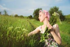 一个愉快的年轻逗人喜爱的女孩的画象有多彩多姿的头发的在乡下公路旁边收集花在日落 的treadled 库存照片