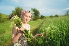 一个愉快的年轻逗人喜爱的女孩的画象有多彩多姿的头发的在乡下公路旁边收集花在日落 的treadled 图库摄影