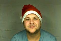 一个愉快的微笑的人在随员和象圣诞老人的红色盖帽的画象保留礼物给年轻圣诞老人在一辆真正的房子或汽车fo 库存照片