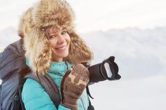 一个愉快的微笑的女孩旅客的特写镜头画象一个大裘皮帽和被编织的手套的有一台照相机的在他的手上 免版税图库摄影