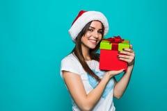 一个愉快的微笑的女孩的画象拿着在绿色背景的礼服的当前箱子 库存照片