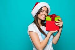 一个愉快的微笑的女孩的画象拿着在绿色背景的礼服的当前箱子 免版税库存照片