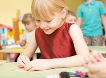 一个愉快的微笑的女孩的画象在幼儿园画明亮的五颜六色的图片并且雕刻从黏土-俄罗斯,莫斯科- 2月0 库存图片