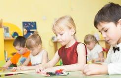 一个愉快的微笑的女孩的画象在幼儿园画明亮的五颜六色的图片并且雕刻从黏土-俄罗斯,莫斯科- 2月0 库存照片