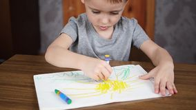 一个愉快的微笑的学龄前儿童男孩坐在桌上并且画与在纸的明亮的铅笔 发展和教育  股票录像