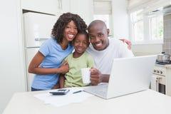 一个愉快的微笑的家庭的画象使用计算机的 免版税库存照片