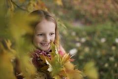 一个愉快的微笑的小女孩的画象在秋天公园 逗人喜爱的四岁享受自然的儿童户外 库存照片