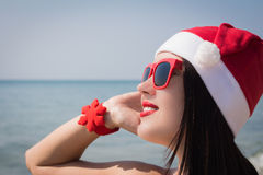 一个愉快的微笑的少妇的画象在圣诞老人帽子 免版税图库摄影