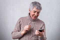 一个愉快的微笑的成熟人在手上的拿着他的智能手机高兴地从他的儿子收到消息 技术,人们,生活 免版税库存照片