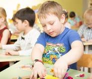 一个愉快的微笑的男孩的画象在幼儿园画明亮的五颜六色的图片并且雕刻从黏土-俄罗斯,莫斯科- 2月04 库存图片