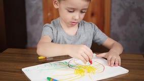 一个愉快的微笑的逗人喜爱的孩子画与蜡笔或铅笔,当在家时坐在桌上 孩子的发展 股票录像