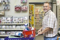 一个愉快的成熟人的侧视图画象有购物车的在五金店 免版税库存照片