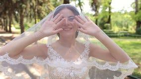一个愉快的新娘的画象面纱的与一个报道的头在夏天公园 股票录像