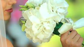 一个愉快的新娘的画象 面纱的一个美丽的新娘拿着花花束  股票视频