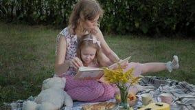 一个愉快的母亲和女儿景色照片在册页读了一本书 家庭在一顿野餐的一个城市公园在一个温暖的晚上在 影视素材