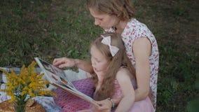 一个愉快的母亲和女儿景色照片在册页读了一本书 家庭在一顿野餐的一个城市公园在一个温暖的晚上在 股票录像