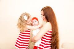 一个愉快的母亲和她的孩子的画象在床上在家 免版税库存照片