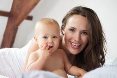 一个愉快的母亲和逗人喜爱的婴孩的画象一起 免版税图库摄影
