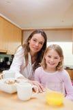 一个愉快的母亲和食用她的女儿早餐 免版税库存照片