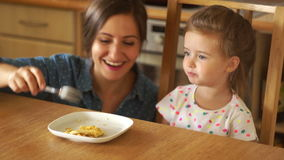 一个愉快的母亲喂养一个小女儿 妈妈播放飞行火箭 女孩宽张她的嘴 母亲亲吻 股票录像
