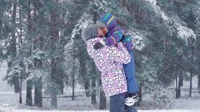 一个愉快的母亲在一冬天多雪的天培养她的在她自己上的儿子并且亲吻他在期间降雪反对 影视素材