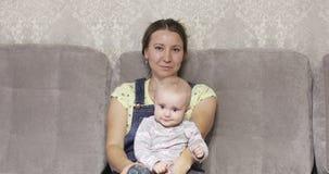 一个愉快的母亲坐长沙发并且抱孩子 小女孩使用与安慰者 股票视频
