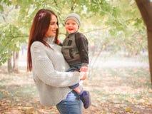 一个愉快的母亲拿着胳膊的儿子,站立在秋天公园 家庭的概念 免版税图库摄影