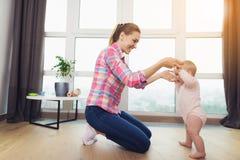 一个愉快的母亲教她的孩子走 她是下跪和抱着婴孩由胳膊 库存照片