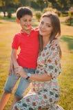 一个愉快的母亲的画象和儿子在一个夏天停放 闩上构成概念系列螺母 免版税库存图片