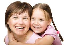 一个愉快的母亲的画象有她的女儿的 免版税库存图片