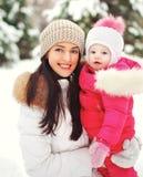 一个愉快的母亲的画象有孩子的户外在冬天 库存图片