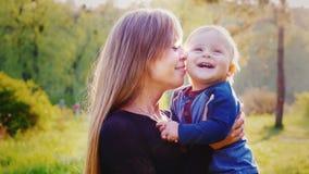 一个愉快的母亲的画象有男婴的 孩子微笑着,两个是非常愉快的 在日落前的美好的照明设备 股票视频
