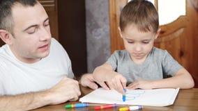 一个愉快的父亲和他小的童颜在册页和凹道与蜡笔或铅笔,当坐在桌时 股票视频