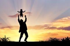 一个愉快的父亲和孩子的剪影 库存照片