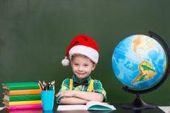 一个愉快的男孩的画象有红色圣诞节帽子的在教室 库存照片