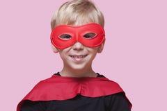 一个愉快的男孩的画象超级英雄服装的在桃红色背景 免版税库存照片