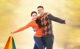 一个愉快的男朋友和女朋友有步行在有coloutful购物袋的秋天公园 免版税库存图片