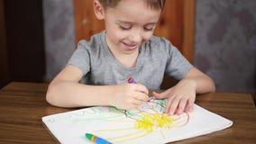 一个愉快的笑的孩子的画象在与明亮的颜色蜡笔或铅笔的一张桌上坐纸 发展和 影视素材