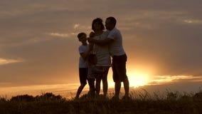 一个愉快的系列的剪影 爸爸,两个孩子拥抱我的母亲在日落 一个愉快的家庭的概念 股票录像