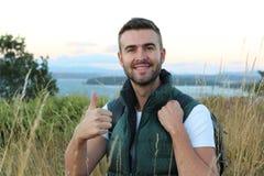 一个愉快的英俊的人的画象有远足入森林的背包的有从山的上面的惊人的看法 免版税图库摄影