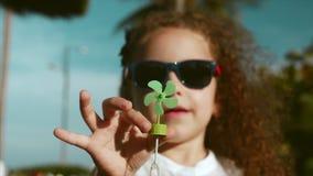 一个愉快的逗人喜爱的小女孩孩子的特写镜头画象有注视着入照相机的卷发和红色太阳镜的一半 股票录像