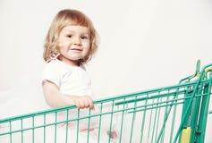 一个愉快的逗人喜爱的小女孩的画象一件白色礼服的在有购物的一辆台车坐白色背景 免版税库存图片