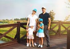 一个愉快的年轻家庭的画象在高尔夫俱乐部的 图库摄影