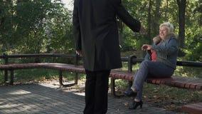 一个成人人接近妇女坐长凳 股票视频