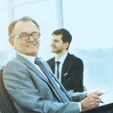 一个成功的商人的画象在背景工作的企业队的办公室 库存照片
