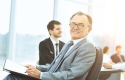 一个成功的商人的画象在背景工作的企业队的办公室 免版税图库摄影