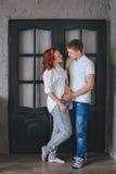 一个成功的年轻人和一名年轻美丽的孕妇 预期婴孩 我们看彼此并且拥抱 免版税库存照片