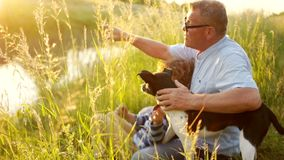 一个成熟人和男孩坐河岸 祖父显示某事到他的孙子手在 股票视频